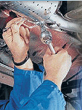 mechanic welding an exhaust